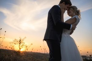 Silhouette of wedding couple in love. Against the setting sun in the field. Lovers embrace girl smiling.